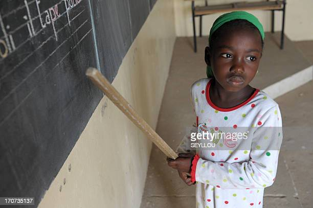 Senegalese 7yearold pupil Ndeye Fatou Ndiaye attends a lesson in her classroom on 10 June 2013 at the FrancoArab school of Diagnel 14km south of...