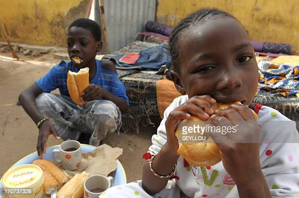 Senegalese 7yearold pupil Ndeye Fatou Ndiaye eats her breakfast with her brother Pape Malick in their home on June 10 in Diagnel 14km south of...