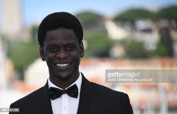 Senegalese actor Souleymane Seye Ndiaye poses on May 23 2017 during a photocall for the film 'Jeune Femme' at the 70th edition of the Cannes Film...