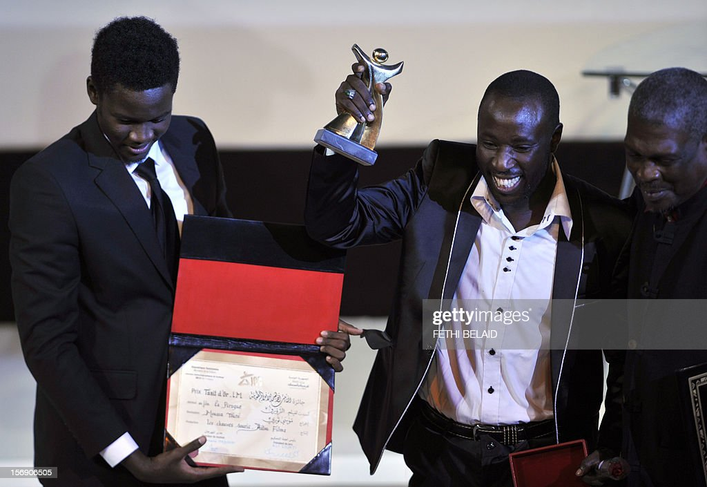 Senegalese actors Babacar Oualy (2nd R) and Laity Fall (L) celebrate with the Gold Tanit award for their roles in the film 'Pirogue', during the closing ceremony of the 28th edition of the Cinematographic Days of Carthage (JCC) film festival on November 24, 2012, in Tunis. AFP PHOTO / FETHI BELAID