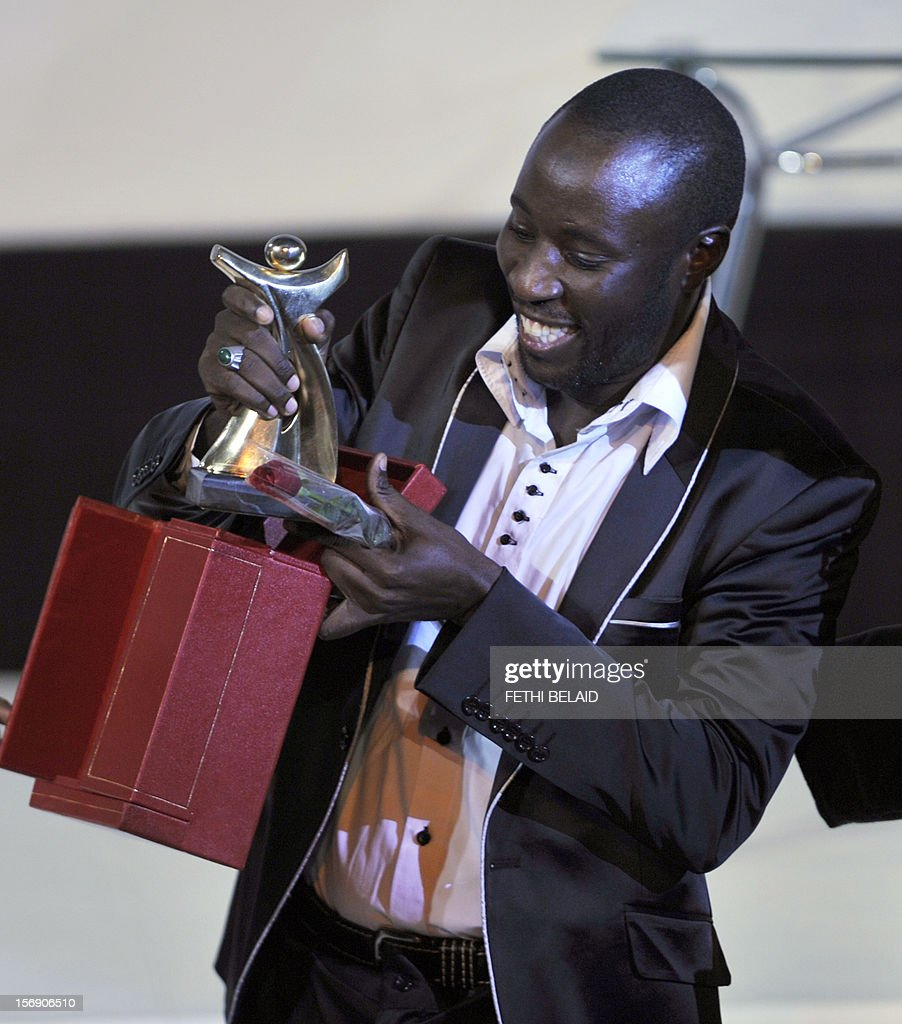Senegalese actors Babacar Oualy celebrates with the Gold Tanit award for his role in the film 'Pirogue', during the closing ceremony of the 28th edition of the Cinematographic Days of Carthage (JCC) film festival on November 24, 2012, in Tunis. AFP PHOTO / FETHI BELAID