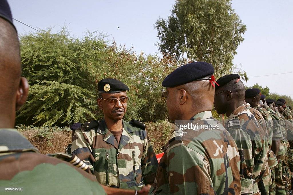 Senegalese army chief, General Mamadou Sow (L) reviews the troops in the Captain Moussa Dioum military camp of Bargny, near Dakar, on February 2, 2013 in Dakar, before their departure for Mali as part of the second contingent of Senegalese troops to back Malian forces. President Francois Hollande arrived in Mali Saturday to push for African troops to replace French forces who led a lightning advance that drove back radical Islamists from the country's desert north. BEHAN