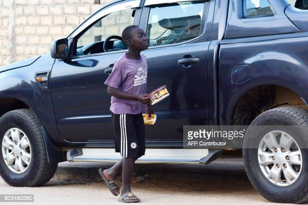 A Senegalese child walks by a car in a street of Guediawaye near Dakar while begging for money or food on July 19 2017 Senegal's 'talibes' children...