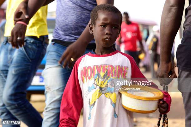 A Senegalese child walks in a street of Guediawaye near Dakar while begging for money or food on July 19 2017 Senegal's 'talibes' children as young...