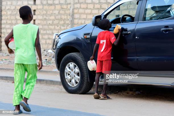 Senegalese children speak to a motorist in a street of Guediawaye near Dakar as they beg for money or food on July 19 2017 Senegal's 'talibes'...