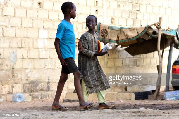 Senegalese children walk in a street of Guediawaye near Dakar as they beg for money or food on July 19 2017 Senegal's 'talibes' children as young as...