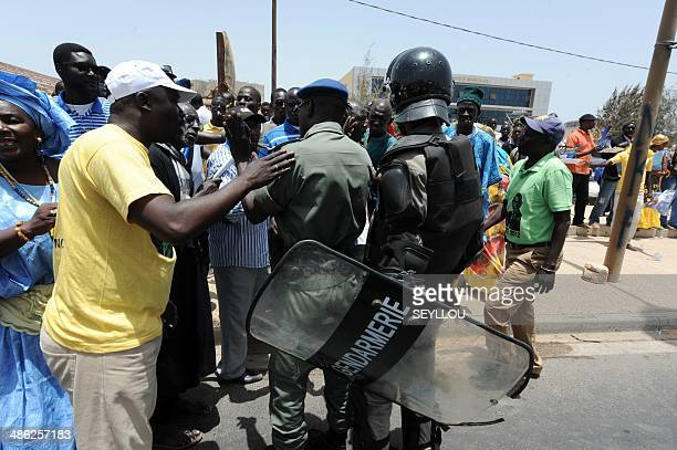 Senegalese gendarmes argue with members and supporters of the Parti Democratique Senegalais holding poster showing their leader former Senegalese...