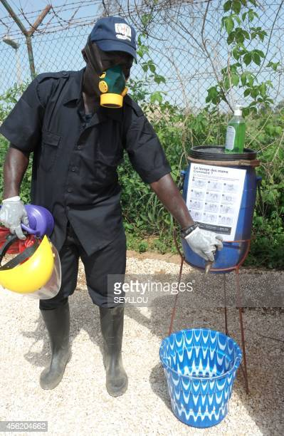 A Senegalese health worker shows a washing station to the press as an World Food Programme aircraft carrying United Nations humanitarian personnel...