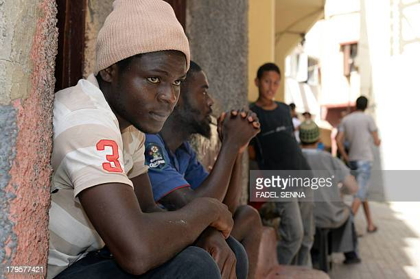 Senegalese immigrants sit in front of a building where they rent rooms in the Takaddum neighbourhood of Rabat on August 23 2013 Following the death...