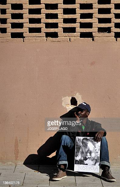 A Senegalese man holds a picture of a compatriot shot dead in Sant Adria del Besos near Barcelona during clashes between a group of subSaharan...