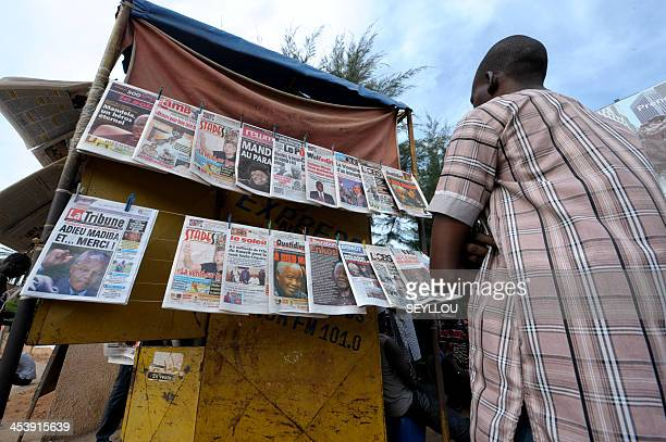 A Senegalese man reads newspapers front pages paying tribute to late President Nelson Mandela are displayed at a newsstand in Dakar Senegal on...
