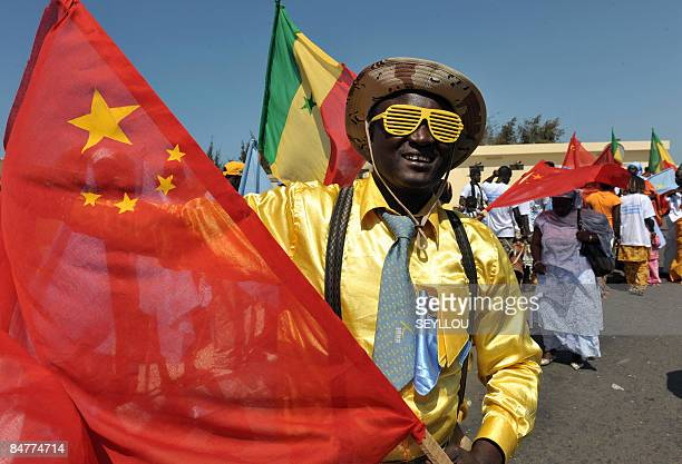 A Senegalese man waves a Chinese flag on February 13 2009 in Dakar as he waits for Chinese President Hu Jintao's arrival from Dakar aiportChina's...