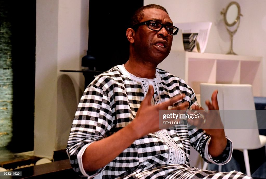 Senegalese musician Youssou N'Dour gestures during an interview on March 13, 2017 at a restaurant in Dakar. /