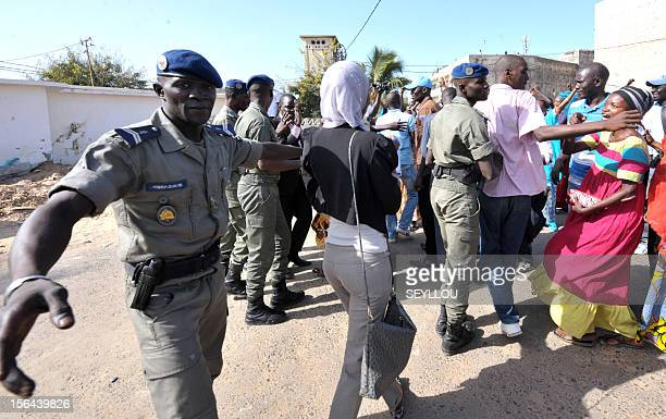 Senegalese paramilitary police push back supporters of the son of Senegal's expresident Abdoulaye Wade Karim Wade as the latter arrives on November...
