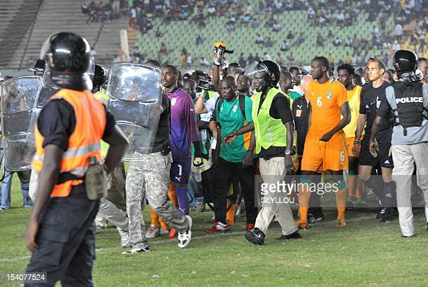 Senegalese police escort Ivory Coast players including Yaya Toure and goalkeeper Baeey Copa as fans rampage on October 13 2012 at Léopold Sédar...