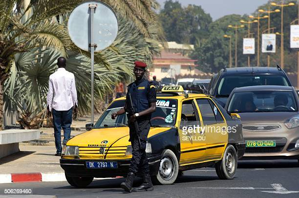 A Senegalese police officer stands guard and inspects vehicles at the entrance of an hotel on January 22 2016 in Dakar Security measures are...