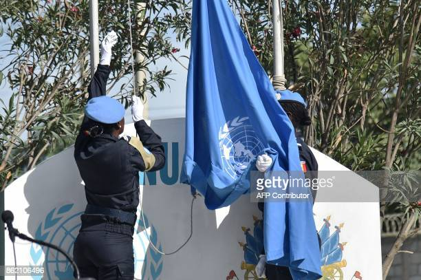 Senegalese police officers of the UN Formed Police Unit raise the UN flag at the opening ceremony of the United Nations Mission in Support of Justice...