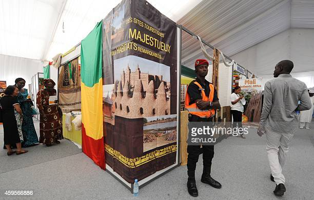 A Senegalese policeman stands as people walk near a booth sporting Mali's flag in the 'Village de la Francophonie' on November 25 2014 in Dakar ahead...