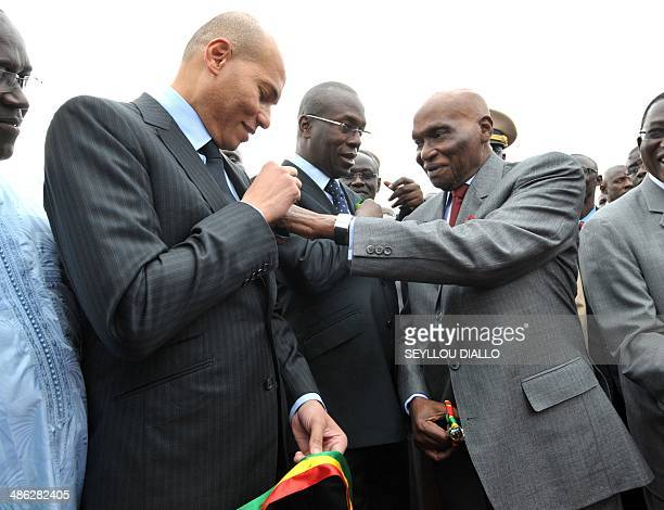 Senegalese President Abdoulaye Wade adjusts a ribbon on his son's jacket Karim Wade during a ceremony to mark the arrival of two Senegal airlines...