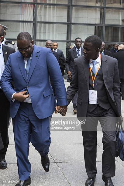 Senegalese president Macky Sall leaves Economy Ministry holding hands with Ibrahima Kobar a board member at Natixis Asset Management after he...