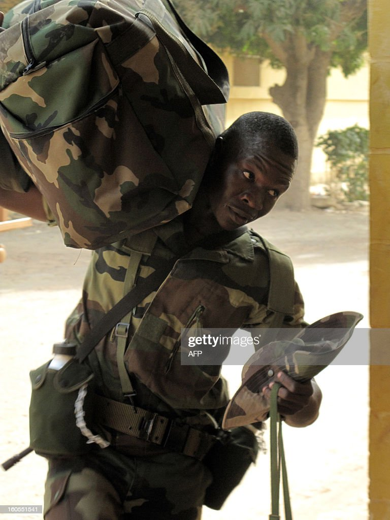 A senegalese soldier carries a bag, at the Captain Moussa Dioum military camp of Bargny, near Dakar, on February 2, 2013, before leaving for Mali as part of the second contingent of Senegalese troops to back Malian forces. French President Francois Hollande received a rapturous welcome in Mali on Saturday as he promised that France would stay as long as necessary to continue the fight against Islamist rebels in the country's north. As troops worked to secure Kidal, the last bastion of radicals who occupied the vast desert north for 10 months before the French army's surprise intervention, Hollande told Malians it was time for Africans to take the lead but that France would not abandon them. AFP PHOTO/Mamadou Toure BEHAN