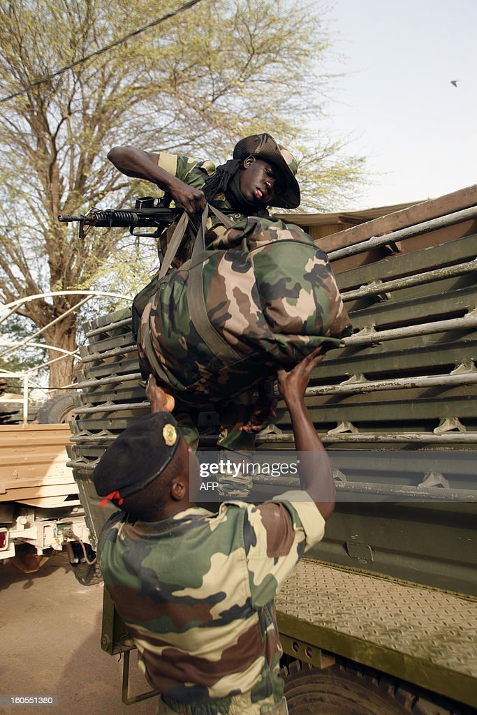 Senegalese soldiers load bags onto a truck , at the Captain Moussa Dioum military camp of Bargny, near Dakar, on February 2, 2013, before leaving for Mali as part of the second contingent of Senegalese troops to back Malian forces. French President Francois Hollande received a rapturous welcome in Mali on Saturday as he promised that France would stay as long as necessary to continue the fight against Islamist rebels in the country's north. As troops worked to secure Kidal, the last bastion of radicals who occupied the vast desert north for 10 months before the French army's surprise intervention, Hollande told Malians it was time for Africans to take the lead but that France would not abandon them. AFP PHOTO/Mamadou Toure BEHAN