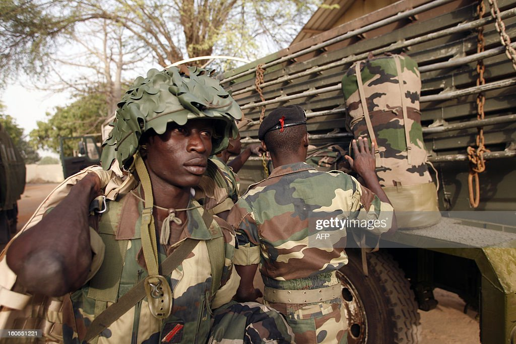 Senegalese soldiers stand next to a truck at the Captain Moussa Dioum military camp of Bargny, near Dakar, on February 2, 2013, before leaving for Mali as part of the second contingent of Senegalese troops to back Malian forces. French President Francois Hollande received a rapturous welcome in Mali on Saturday as he promised that France would stay as long as necessary to continue the fight against Islamist rebels in the country's north. As troops worked to secure Kidal, the last bastion of radicals who occupied the vast desert north for 10 months before the French army's surprise intervention, Hollande told Malians it was time for Africans to take the lead but that France would not abandon them. AFP PHOTO/Mamadou Toure BEHAN