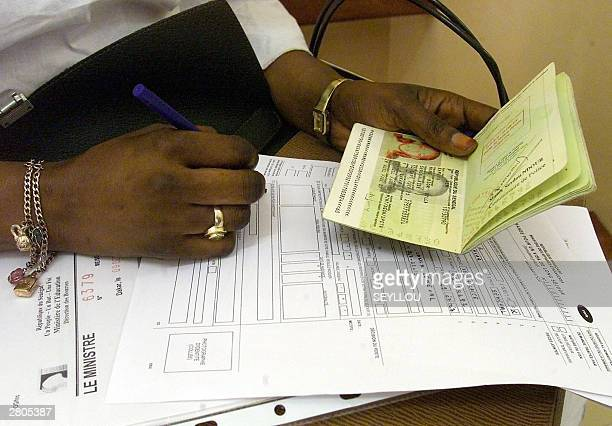 Senegalese woman fills the required papers for a French visa at the French consulate in Dakar 12 December 2003 where French Interior Minister Nicolas...