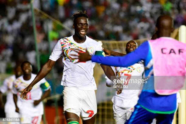 Senegal's defender Kara Mbodji celebrates with teammates after winning the FIFA 2018 World Cup Africa Group D qualifying football match between South...