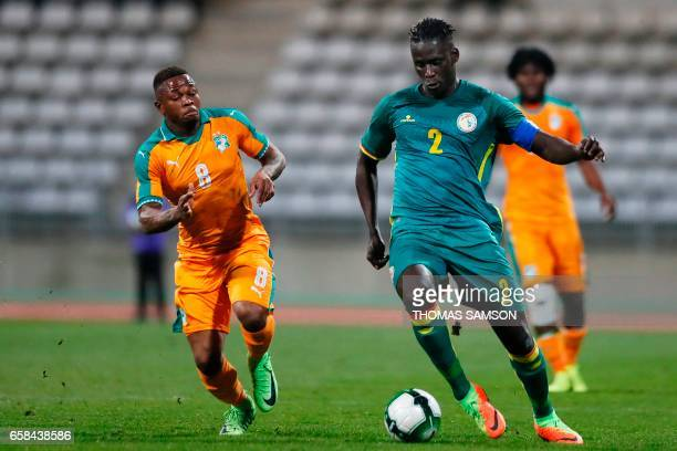Senegal's defender Kara Mbodji vies with Ivory Coast's midfielder Zoro Cyriac Gohibi during the friendly football match Ivory Coast vs Senegal on...