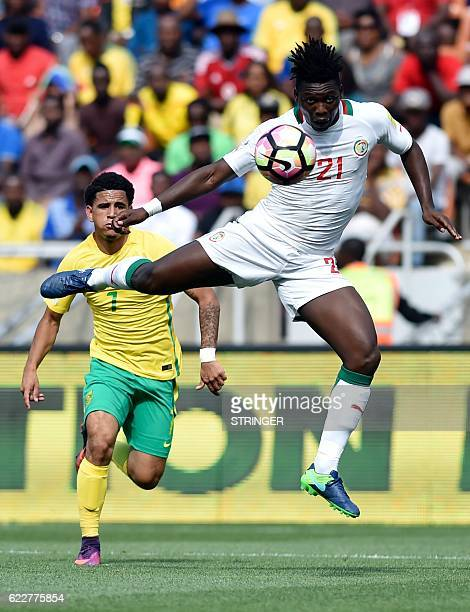 Senegal's Lamine Gassama jumps for the ball next to South African Keegan Dolly during the 2018 World Cup qualifying football match between South...