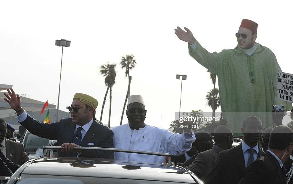 Senegal's President Macky Sall (C) and Moroccan King Mohammed VI (L) wave to people, one of them holding a cardboard effigy of the King, as they stand in a vehicle shortly after the king's arrival at Dakar's airport on March 15, 2013.