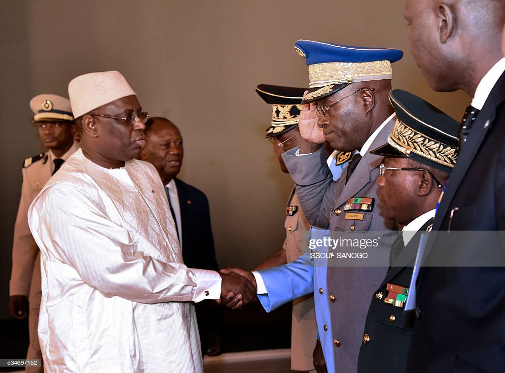 Senegal's President Macky Sall (L) shake hands with Ivory Coast's army officers walks during a security meeting of the ministers of Security Defence and Security of the West African Economic and Monetary Union zone (UEMOA) in Abidjan on May 27, 2016. / AFP / ISSOUF