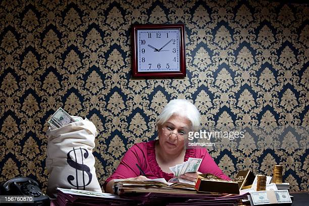 Senior accountant woman counting money on  desk