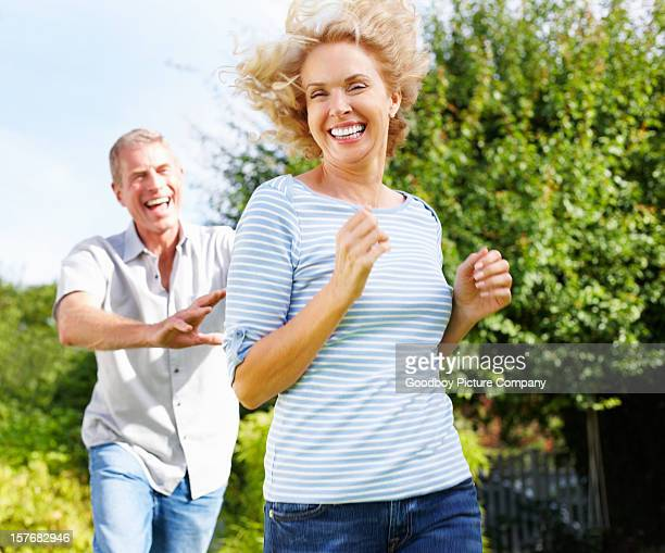Senior active man running behind mature woman