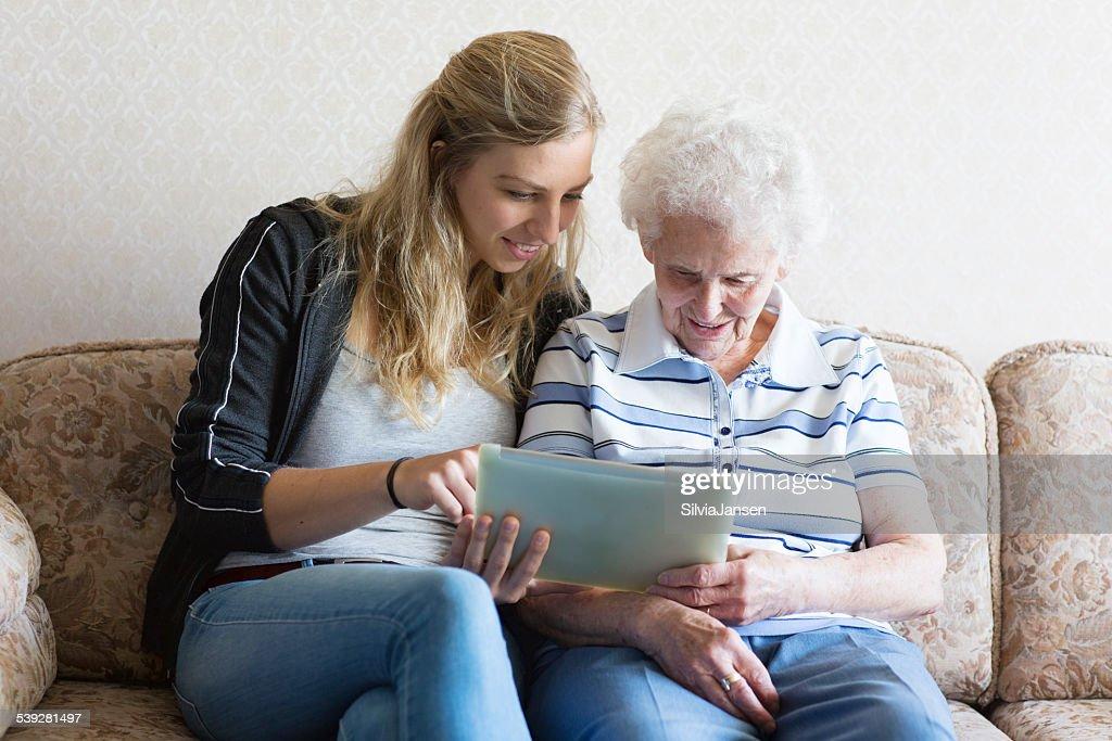 senior adult and caregiver using digital tablet