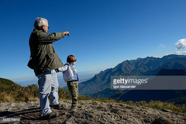 Senior adult and little boy looking at the mountains in Itatiaia National Park