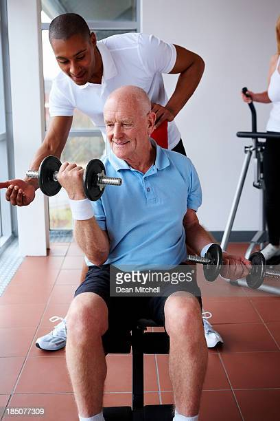 Senior adult assisted by young trainer in gym