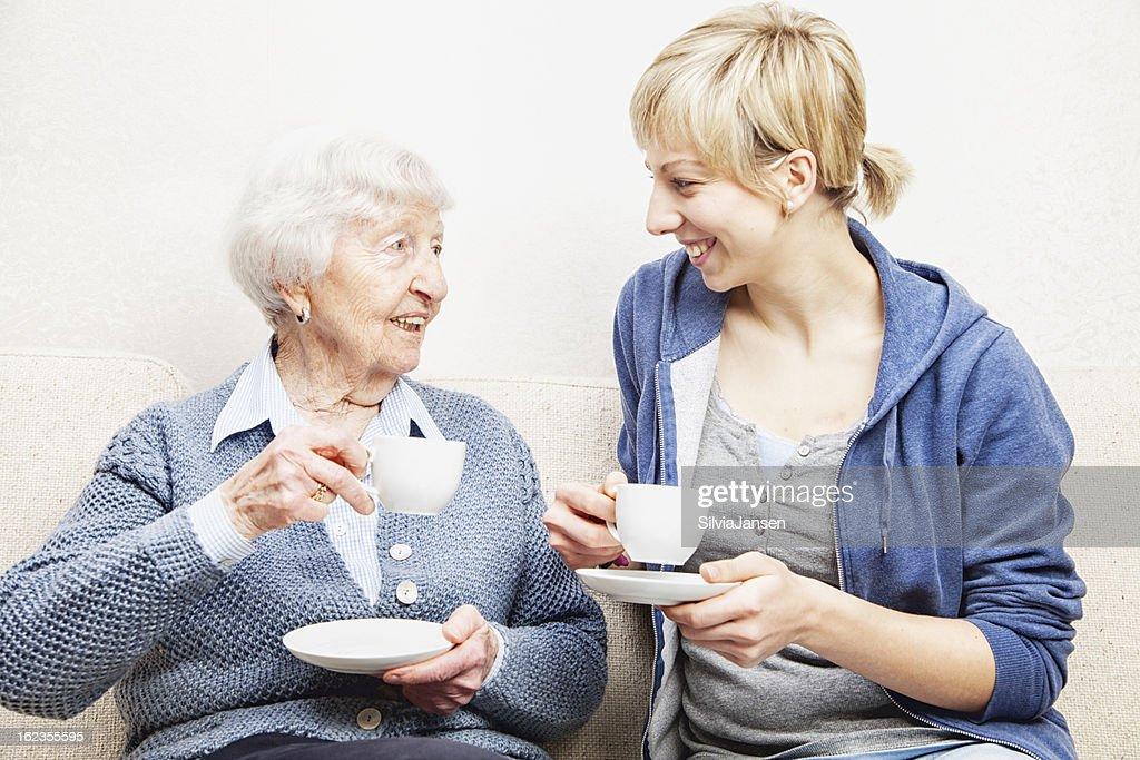senior adult caregiver talking drinking coffee