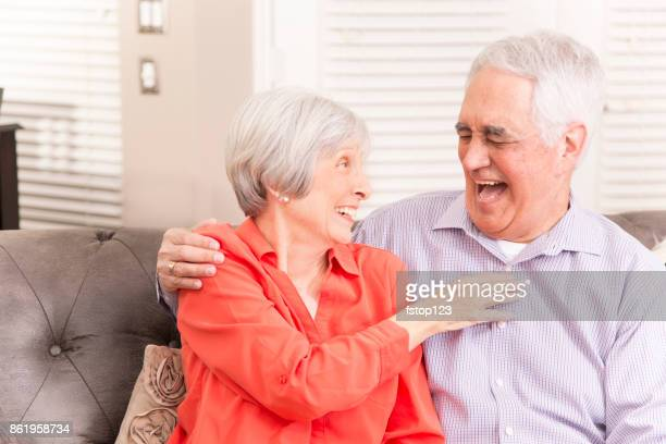 Senior adult couple at home laughing.