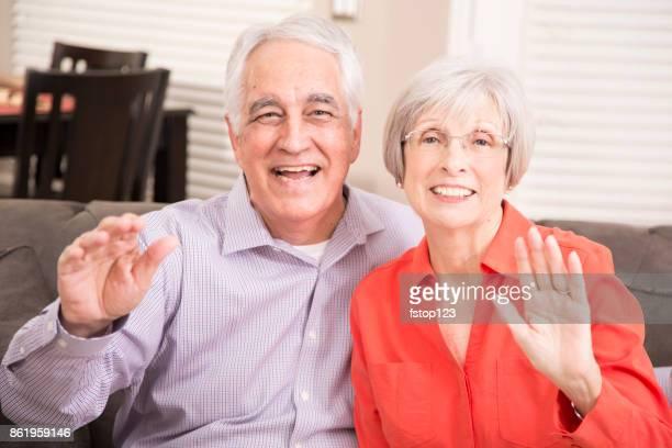 Senior adult couple at home waving to camera.