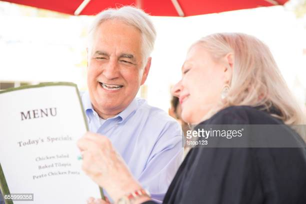 Senior adult couple enjoys dining at outdoor cafe.