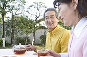 A Senior Adult Couple Having a Tea Break in a Garden, Side View