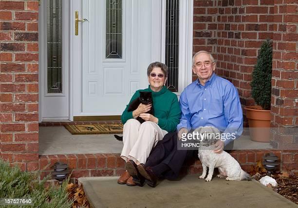 Senior adulte Couple assis en face de la maison avec les animaux de compagnie