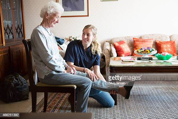 senior adult doing physiotherapy supported by therapist
