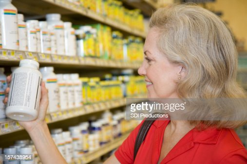 Senior Adult Female Reading Contents of Vitamin Bottle