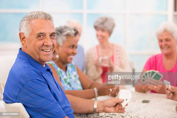 Senior adult friends playing cards. Home or community center setting.