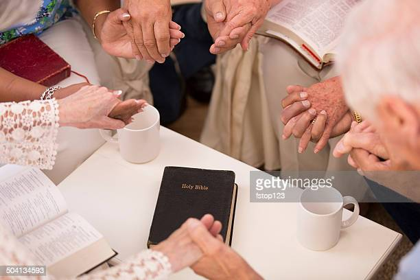 Senior adult friends pray during bible study group.