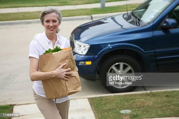 Senior Adult Happily Carrying Groceries in from Her Car