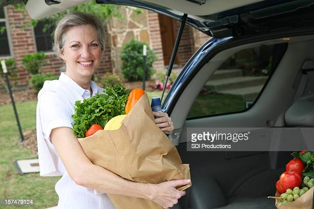 Senior Adult Happily Unloading Bag of Groceries from car trunk